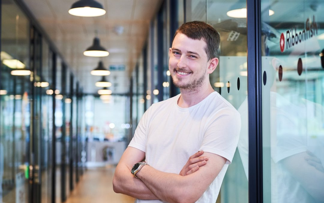Image of Tristan Hudson, Software Developer at Ribbonfish, standing smiling and relaxed in the offices