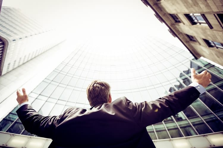 Image of man opening arms up in a business sector architectural city scape